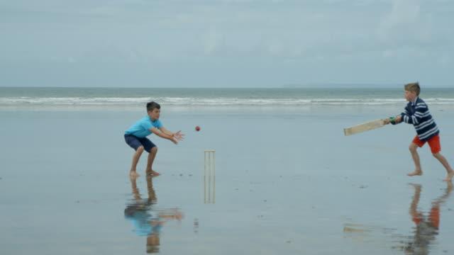 vídeos y material grabado en eventos de stock de dos niños pequeños jugando beach cricket uno tratando de entrar y otros hits de los tocones. - críquet