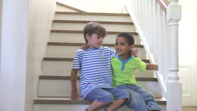 Two Young Boys Playing On Stairs At Home video