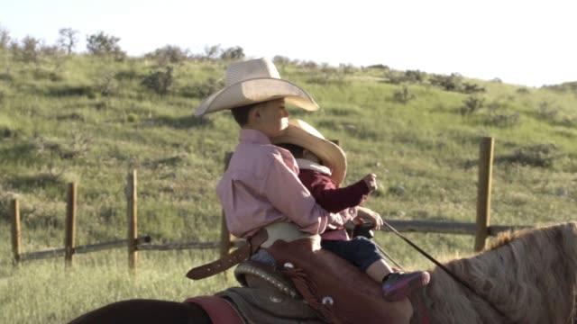 zwei jungen auf einem pferd in einem feld - ranch stock-videos und b-roll-filmmaterial