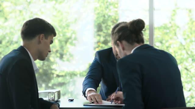 2 人の若いビジネスマンがオフィスでセールスマンと巧妙な取り引きを作っています。 ビデオ