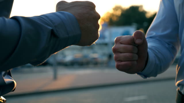 two young businessmen making fist bump as symbol of giving respect and as a form of greeting at city street. successful colleagues celebrating success against the background of cars parking. close up - pugno video stock e b–roll