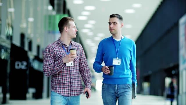 idカードを持った2人の若いビジネスマンがオフィスのロビーを歩き、コーヒーを飲みながら話をしている。携帯電話とノートパソコンを持っている男性。ビジネスイベントの出席者は、コー� - メダル点の映像素材/bロール