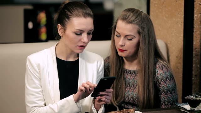 Two young businesswomen meet in restaurant video