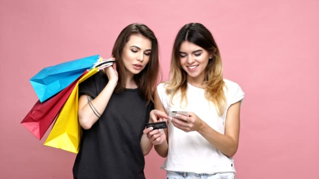Two young casual girls with shopping bags using credit card and mobile phone for shopping online isolated over pink background video