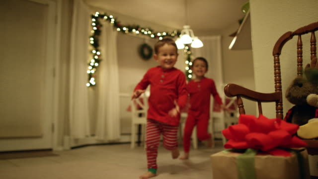 two young (three and five year-old) caucasian boys in pajamas run to the christmas tree and excitedly pick up christmas presents from underneath the christmas tree on christmas day - уютный стоковые видео и кадры b-roll