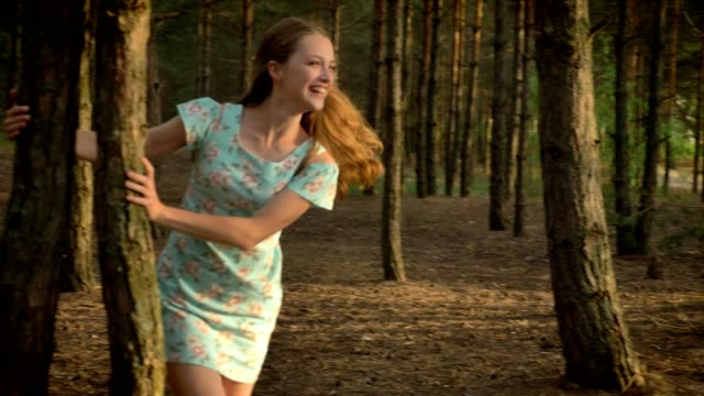 Two young Caucasian girls in dresses running through forest, fooling around, nature in the background video