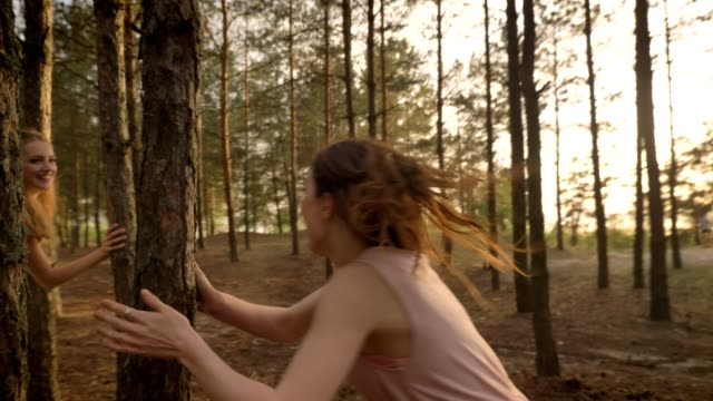 Two young Caucasian girls in dresses running through forest, playing catch, fooling around, nature in the background video