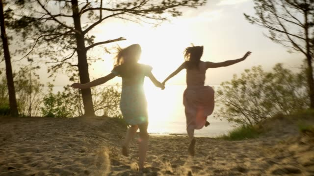 Two young Caucasian girls in dresses running through the sand in the sea, laughing, hugging, sunlight, sunset video