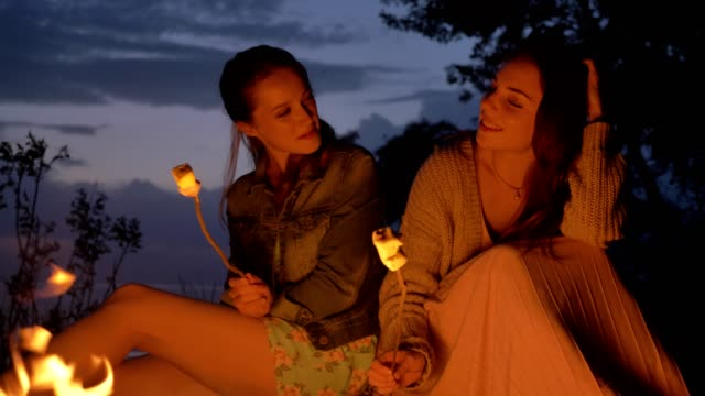 Two young Caucasian girls sitting by fire in evening in nature, preparing a marshmelow, looking at open fire, thinking - video