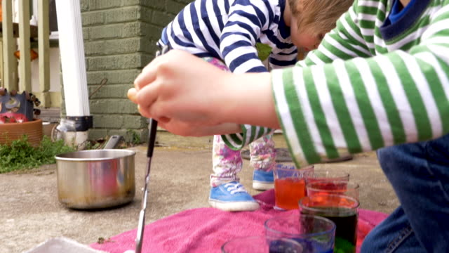 Two young children painting and dyeing easter eggs together outside video