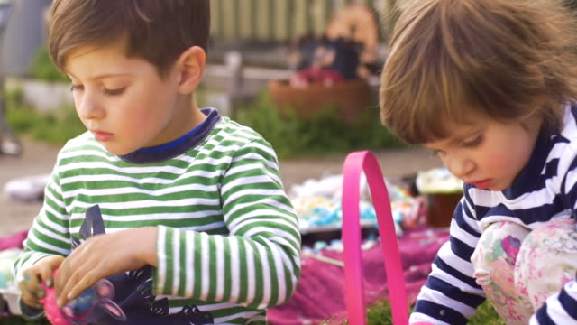 Two young children playing with toys in a basket outside together video