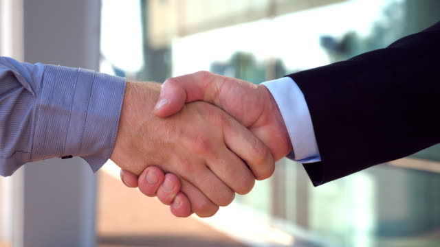 Two young colleagues shaking hands after successful deal near office building. Confident businessmen congratulating each other in urban environment. Handshake of business partners. Side view Close up