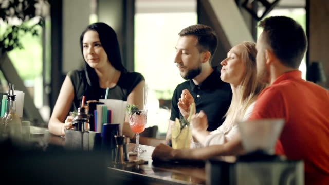 Two young couples drinking cocktails at the bar counter. Four students spending time together celebrating holidays. Company of men and women sitting and laughing happily video
