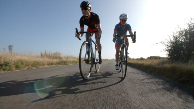 two young cyclists peddle along a country road. - veicolo a due ruote video stock e b–roll