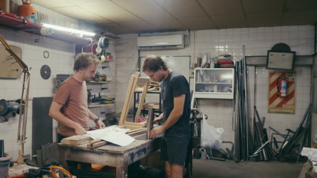 Two young designers crafting a new product in workshop