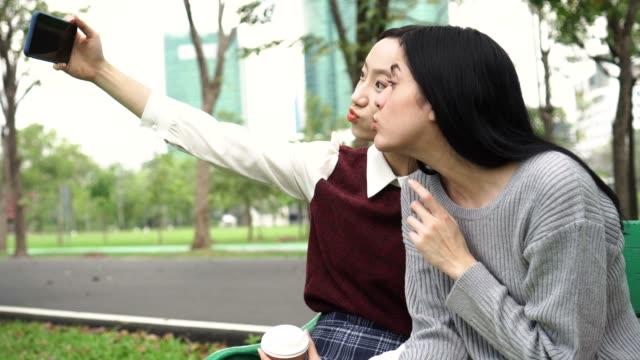 stockvideo's en b-roll-footage met het nemen van een selfie foto in openbaar park buiten twee jonge vriendinnen voor divers gebruik. multi-etnische diversiteit. - oost aziatische cultuur