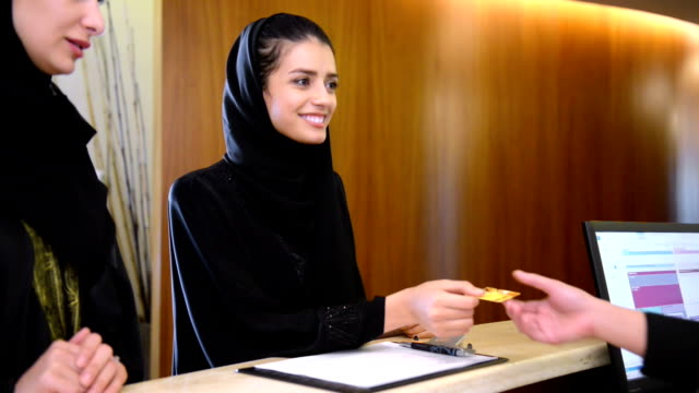 two young emirati women paying via credit card - emirati woman 個影片檔及 b 捲影像