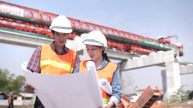 stockvideo's en b-roll-footage met twee jonge ingenieurs, praten met elkaar in bouwplaats, achtergrond grote kraan, ze dragen van veiligheidsuitrusting - chemische fabriek