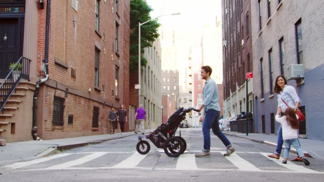 Two young families crossing a street in Brooklyn