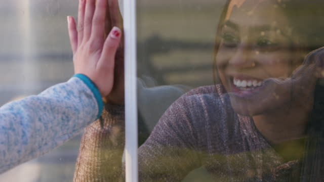 Two Young Female Friends Connecting Through a Window