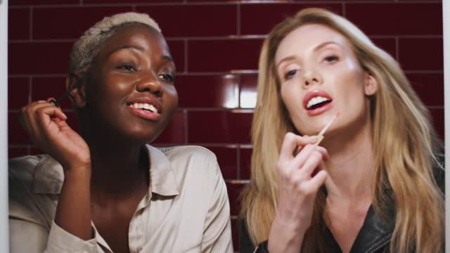 vídeos de stock, filmes e b-roll de duas jovens amigas fazendo maquiagem refletidas no espelho do banheiro em clube - amizade feminina