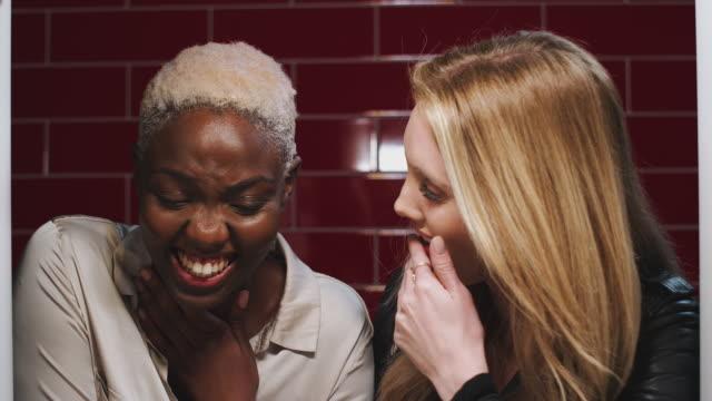 vídeos de stock, filmes e b-roll de duas jovens amigas olhando mensagens no celular refletidas no espelho do banheiro em clube - amizade feminina