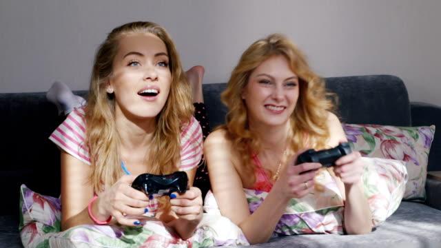 vídeos de stock, filmes e b-roll de dois jovens amigos femininos jogando no console do computador. deitada na cama em casa de pijama - pré estreia