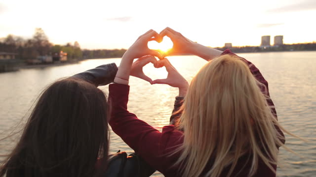 Two young females making heart shape with their hands. video