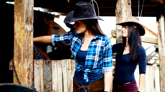 Two young females with their horses in a barn video