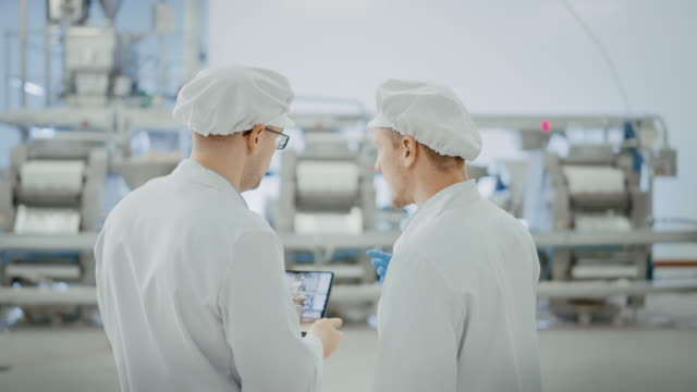 Video Two Young Food Factory Employees Discuss Work-Related Matters. Male Technician or Quality Manager Uses a Tablet Computer for Work. They Wear White Sanitary Hat and Work Robes.