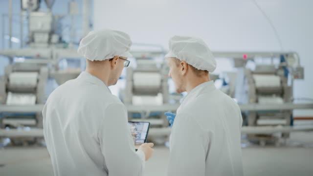 i̇ki genç gıda fabrikası çalışanları iş ile ilgili konuları tartışır. erkek teknisyeni veya kalite yöneticisi çalışma için tablet bilgisayar kullanır. onlar beyaz sıhhi şapka ve iş elbiseler giymek. - hijyen stok videoları ve detay görüntü çekimi