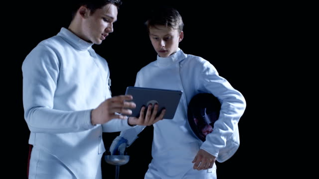 Two Young Fully Equipped Fencers Use Tablet Computer To Learn More About Strategy, Attack and Defense in Fencing. Shot Isolated on Black Background. video
