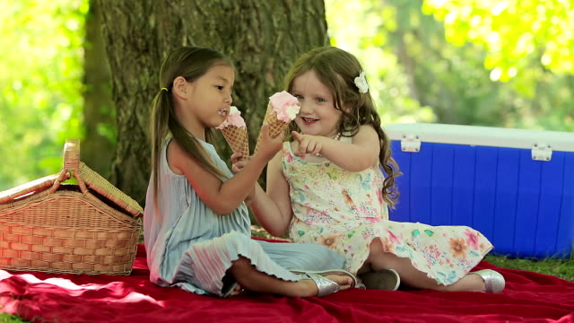 Two young girl friends eat ice cream video