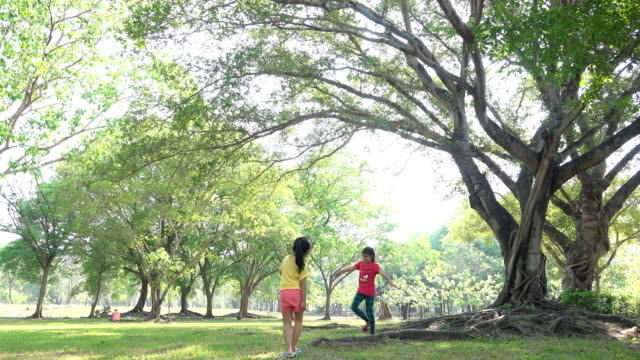 Two Young girl walking under the tree in the park