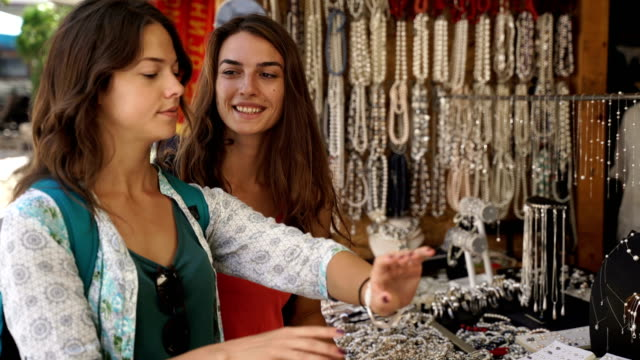 Two young girls buying souvenirs on vacation