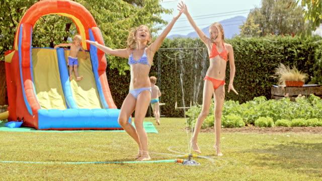 rallent due giovani ragazze ballando in acqua di irrigazione - 8 9 anni video stock e b–roll