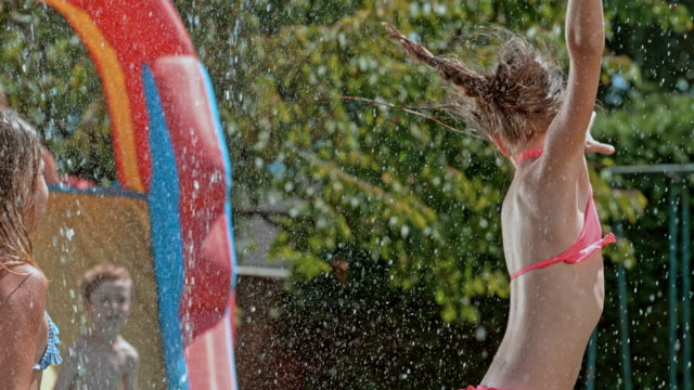 SLO MO Two young girls jumping over the water sprinkler at a garden party video