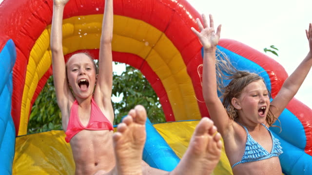 SLO MO Two young girls sliding off inflatable water slide video