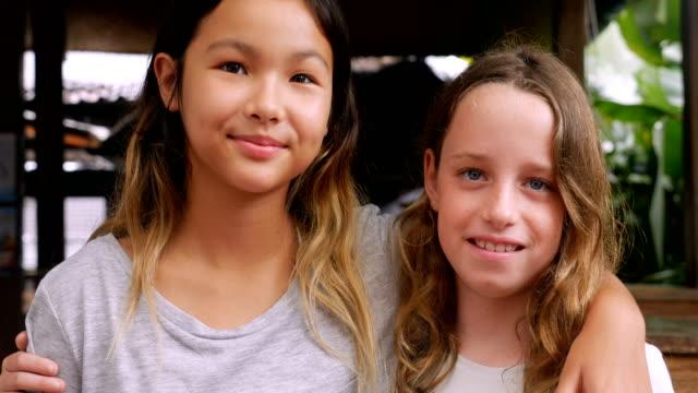 zwei junge mädchen lächeln mit den armen um die schultern - ferienlager stock-videos und b-roll-filmmaterial