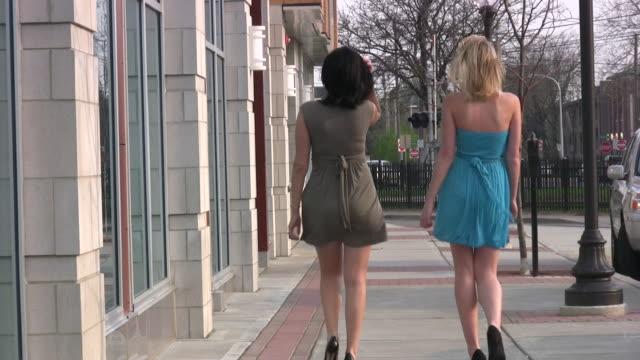 Two young girls women walking. Sexy short dresses. Shopping. video