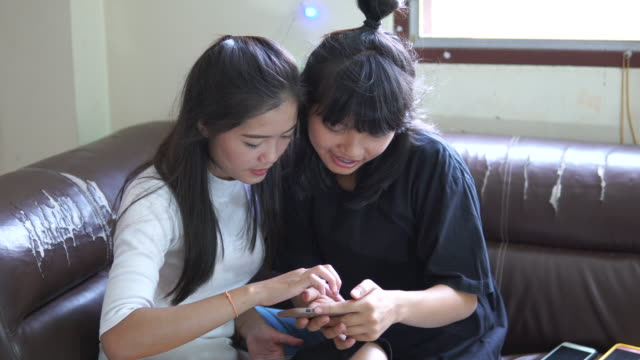 Two young happy girls are using a smartphone at home
