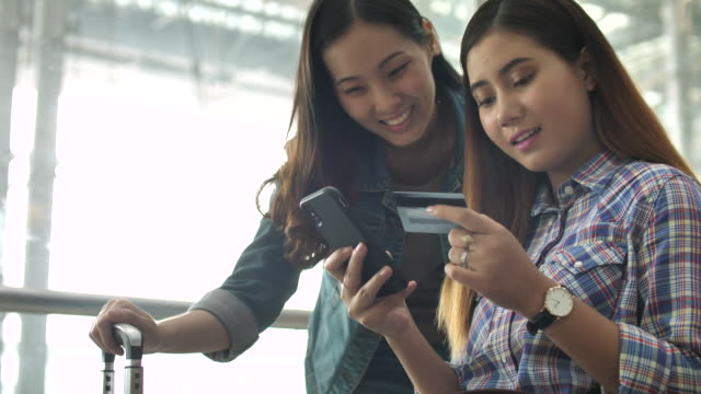 Two young happy girls Online Shopping on smartphone