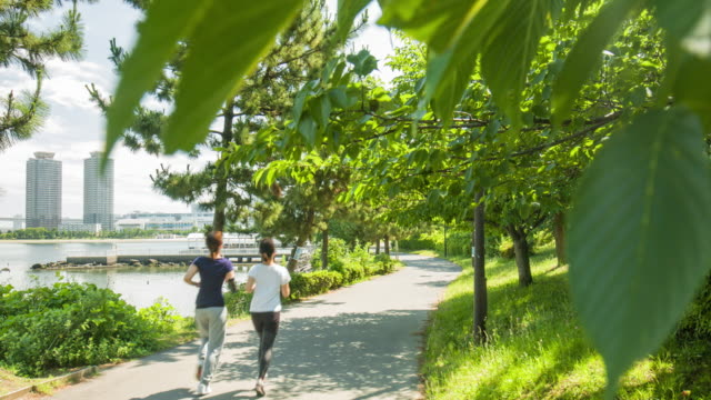 Two young Japanese women running in the park video