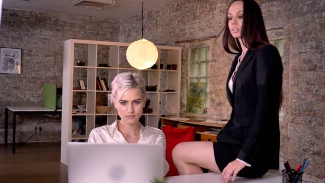 stockvideo's en b-roll-footage met twee jonge lesbiennes in kantoor, blonde mooie vrouw aanraken van een andere vrouw, zittend op tafel - verleiding