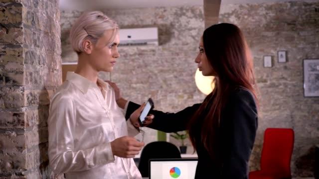 stockvideo's en b-roll-footage met twee jonge lesbiennes in kantoor, vertrouwen vrouw andere vrouw duwen tegen muur, sexy en aantrekkelijk - verleiding