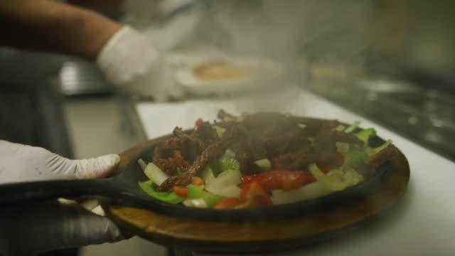 vídeos y material grabado en eventos de stock de dos cocineros mexicanos macho joven en un restaurante mexicano preparan platos al vapor de fajitas en una cocina comercial - comida mexicana