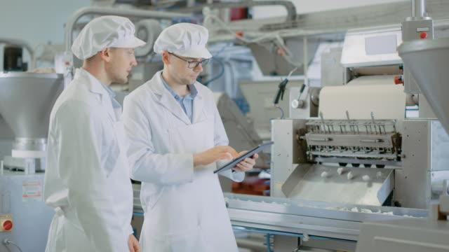 två unga manliga kvalitets handledare eller livsmedels tekniker inspekterar automatiserad produktion vid en dumpling food factory. anställd använder en tablet pc för arbete. de bär vita arbets dräkter. - livsmedelstillverkningsfabrik bildbanksvideor och videomaterial från bakom kulisserna