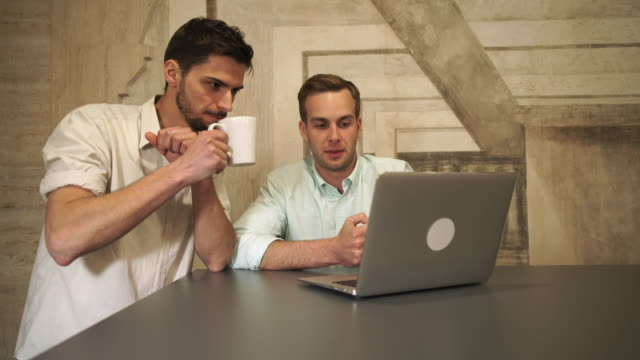 Two young man in the coffee house looking on the screen computer and talking video