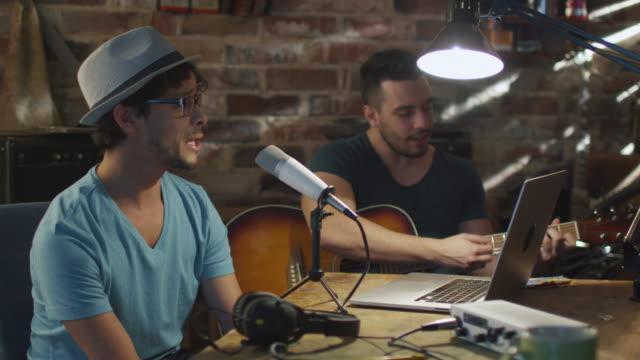 vidéos et rushes de deux jeune homme chanter et jouer de la guitare tout en enregistrant une chanson dans un home studio dans un garage. - podcasting