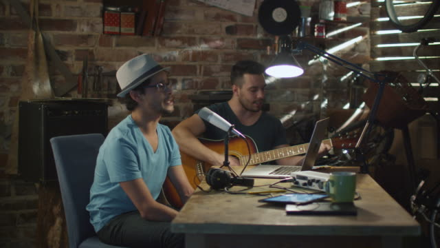 Two young man sing and play guitar while recording a song in a home studio in a garage. video